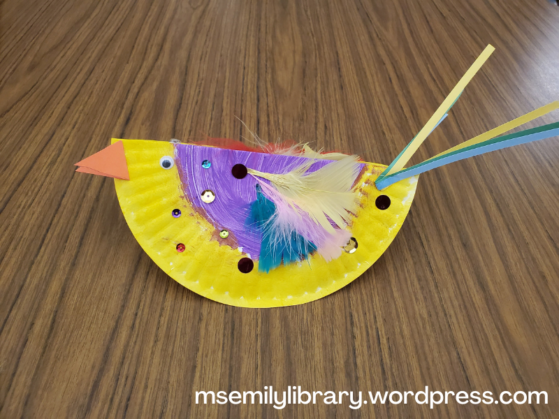 paper plate craft of a bird.  plate is painted yellow and purple, has long tailfeathers, feathers glued to the body, and sequins.